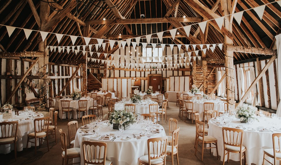 The rustic wedding barn is set up for the wedding breakfast at Clock Barn -  Clock Barn Weddings